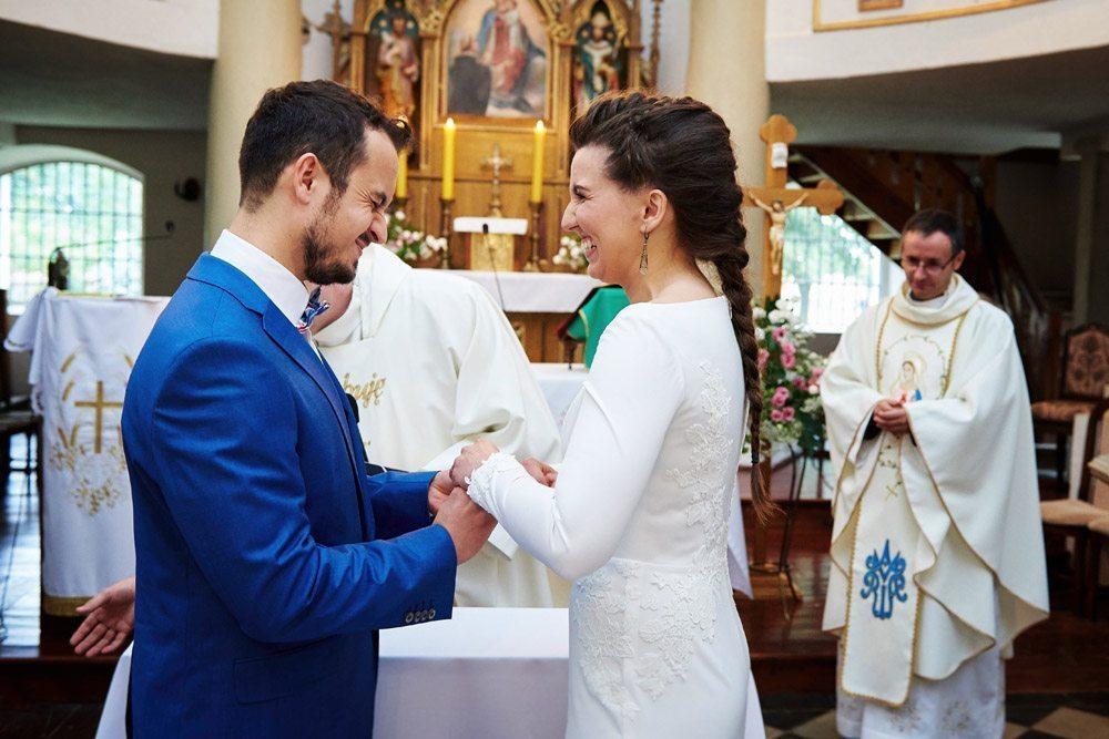 uśmiechnięta para młoda przy zakładaniu obrączek - zdjęcia ślubne wrocław