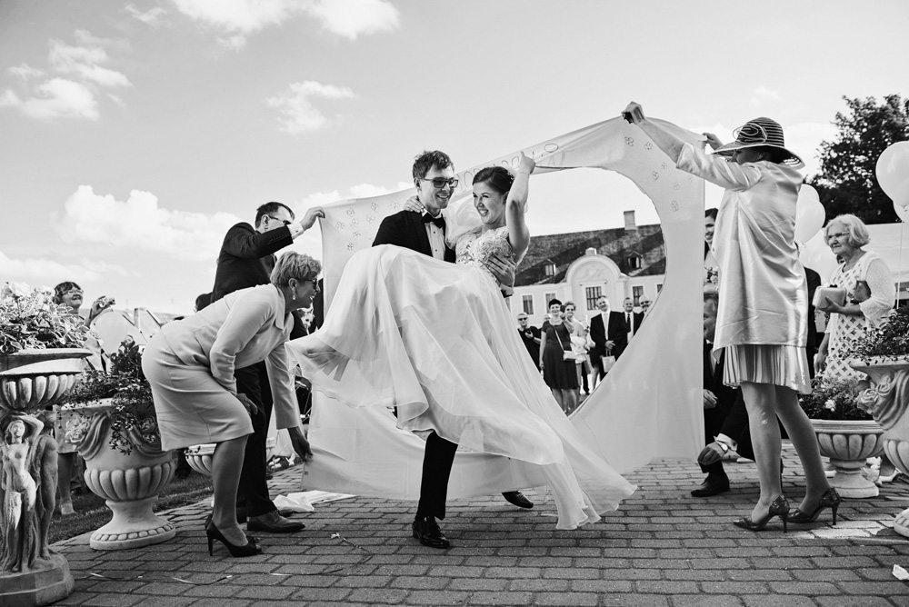 Pan Młody wnosi na rękach Panią Młodą na wesele