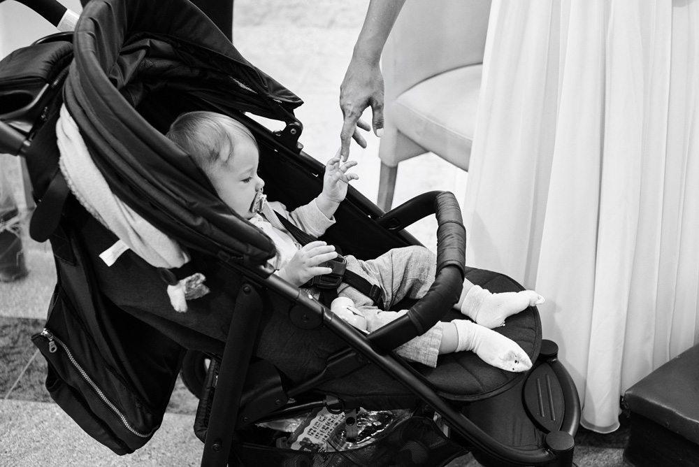 małe dziecko w wózeczku łapie Panne Młodą za palec