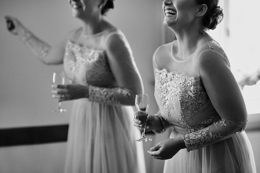 śmiejące się druhny z kieliszkami szampana w ręce