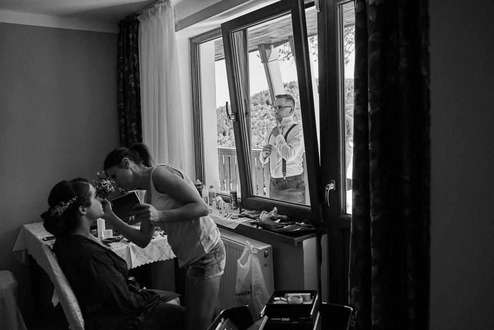 wizażystka maluje Pannę Młodą, za oknem Pan Młody zakłada muszkę