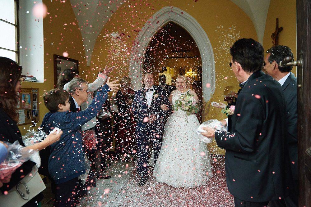 Para Młoda obrzucona płatkami róż przy wyjściu z kościoła