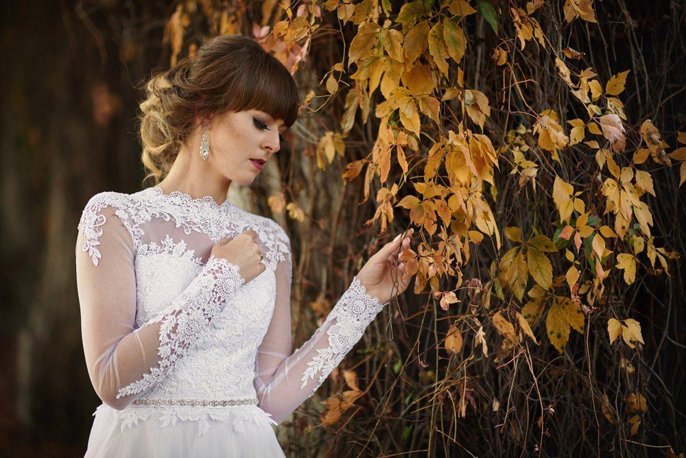 dziewczyna w białej koronkowej sukni ślubnej przy żółtych liściach bluszczu