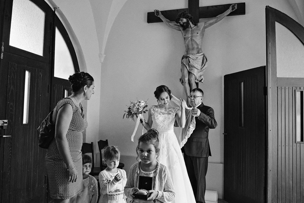 ojciec poprawia welon panny młodej przed wejściem do kościoła