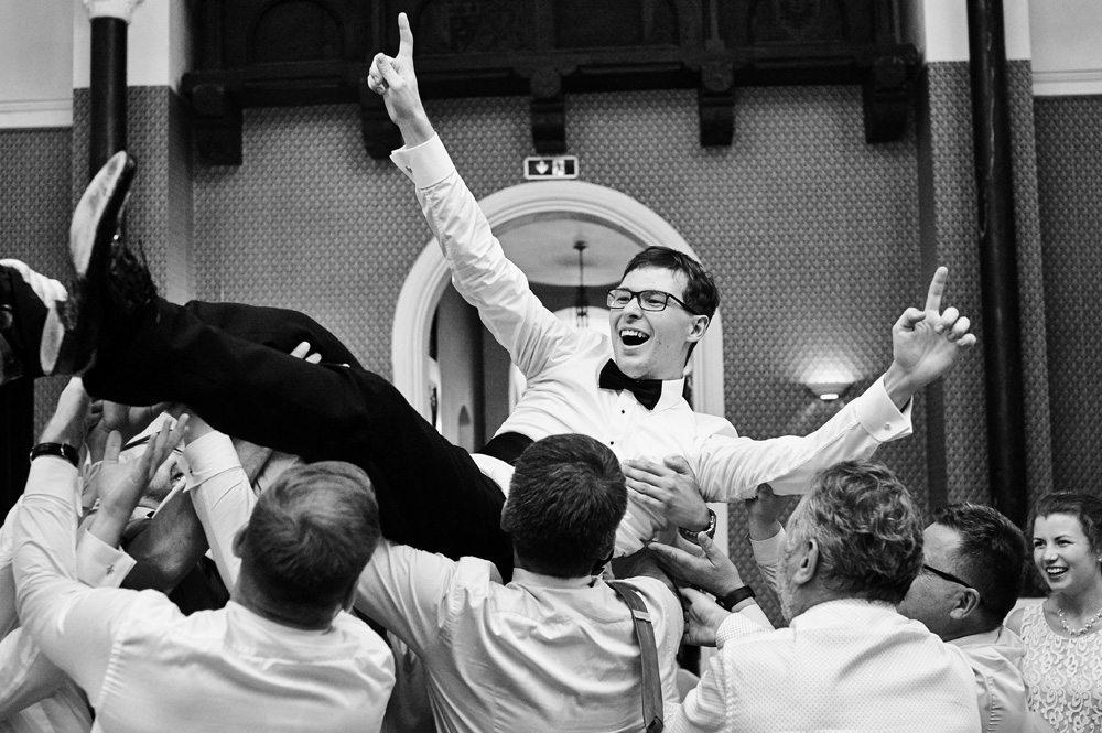 fotografia z zabawy weselnej gdy Pan Młody podrzucany do góry