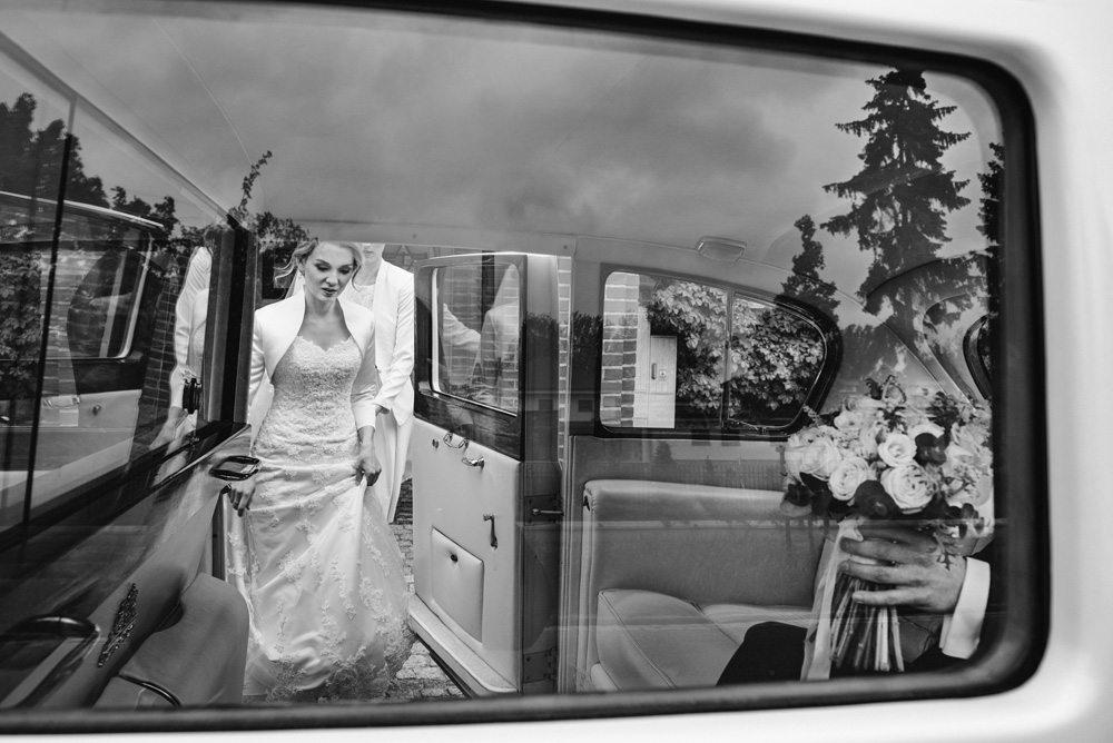 dziewczyna w sukni ślubnej wsiada do samochodu gdzie czeka narzeczony z bukietem