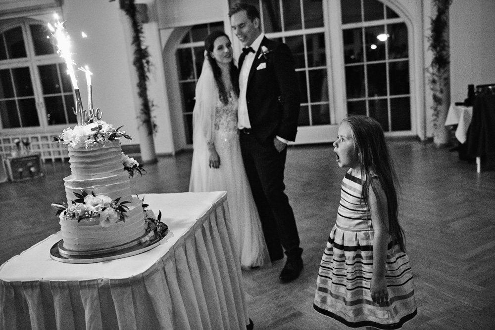 dziewczynka zaskoczona patrzy na tort weselny