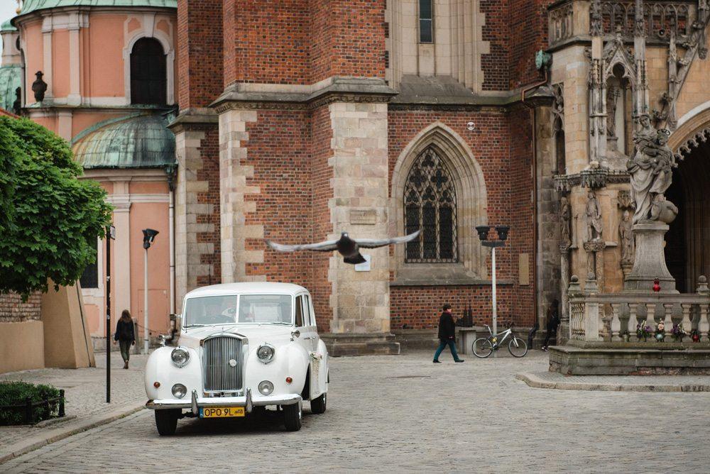 białe zabytkowe auto na ślub jedzie koło Katedry we Wrocławiu