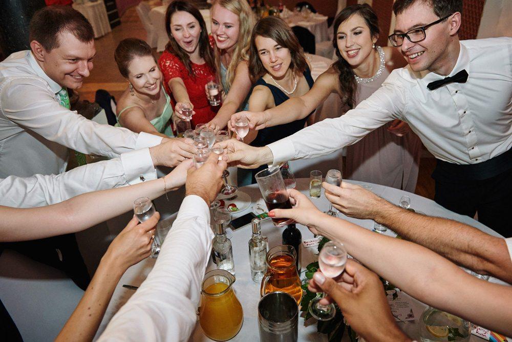 goście na ślubie stukają się kieliszkami przy okrągłym stole