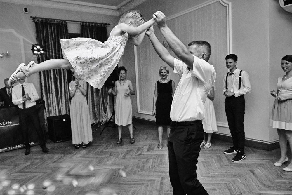 ojciec podrzuca córkę podczas tańca