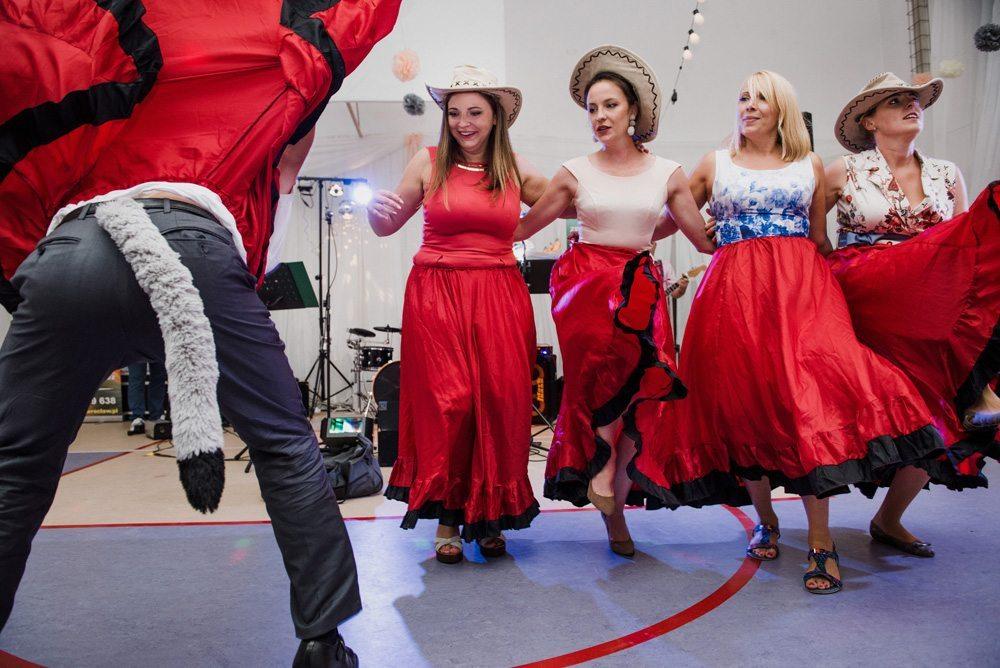 cztery kobiety w czerwonych spódnicach tańczą kankana na weselu