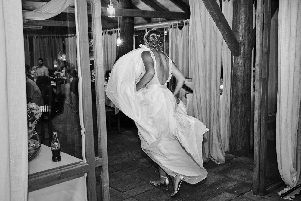 pani młoda wchodzi na salę weselną z podwianą suknią