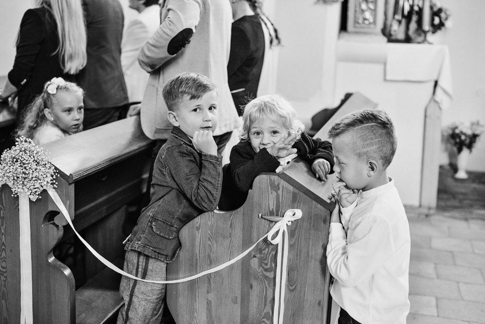 trzech małych chłopców w ławce w kościele