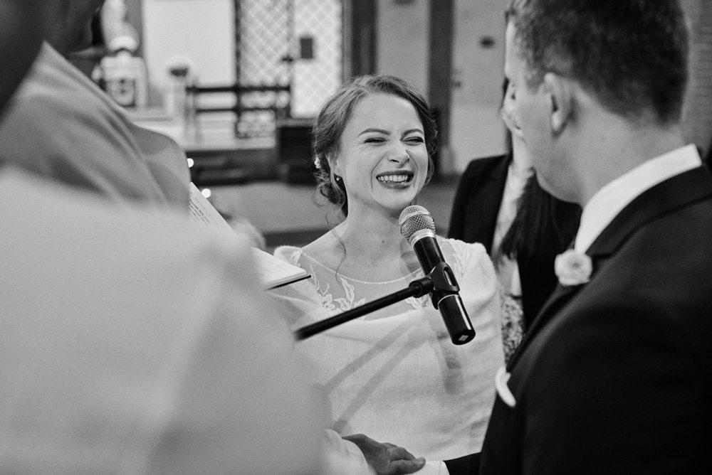 panna młoda śmieje się podczas przysięgi małżeńskiej
