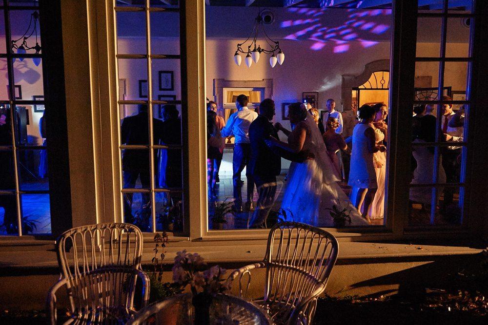 zdjęcie ślubne przez okno tańczącej pary młodej