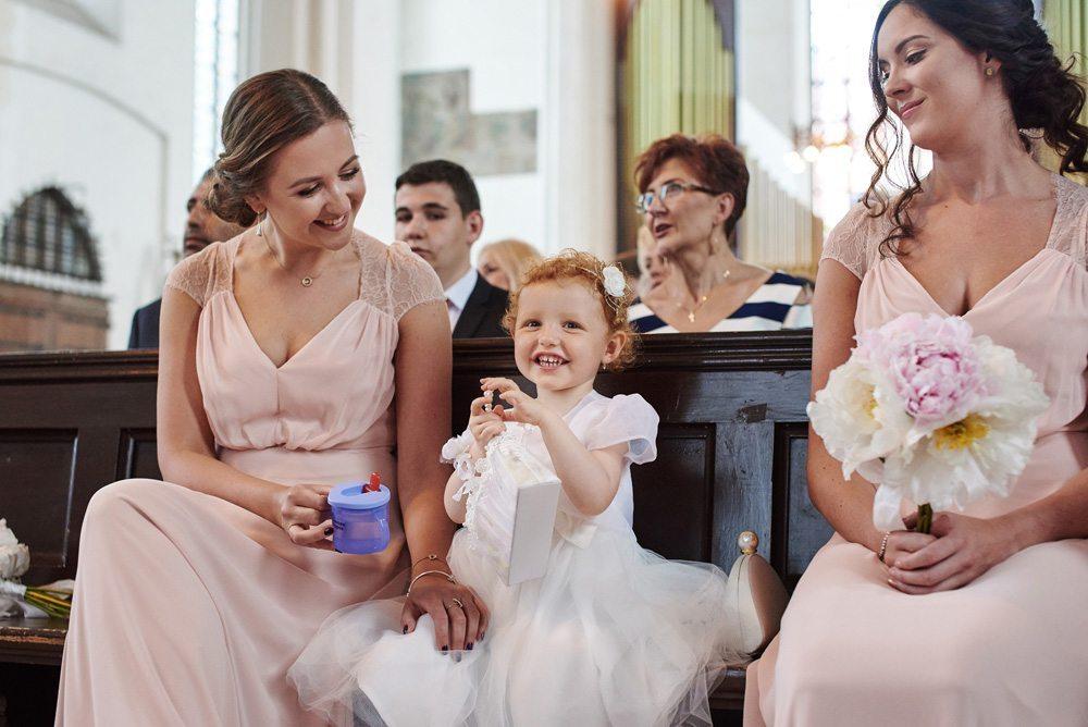 mała dziewczynka z rudymi włosami siedzi pomiędzy druhnami podczas ślubu
