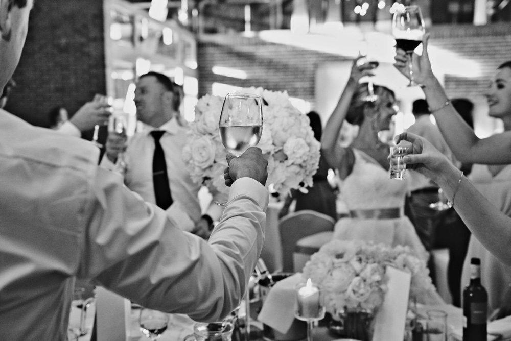 goście podnoszą toast weselny do fotografii ślubnej