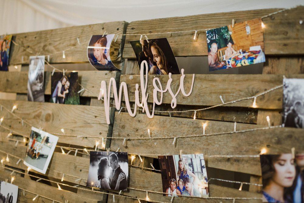 zdjęcia z sesji narzeczeńskiej zawieszone na paletach i napis miłość