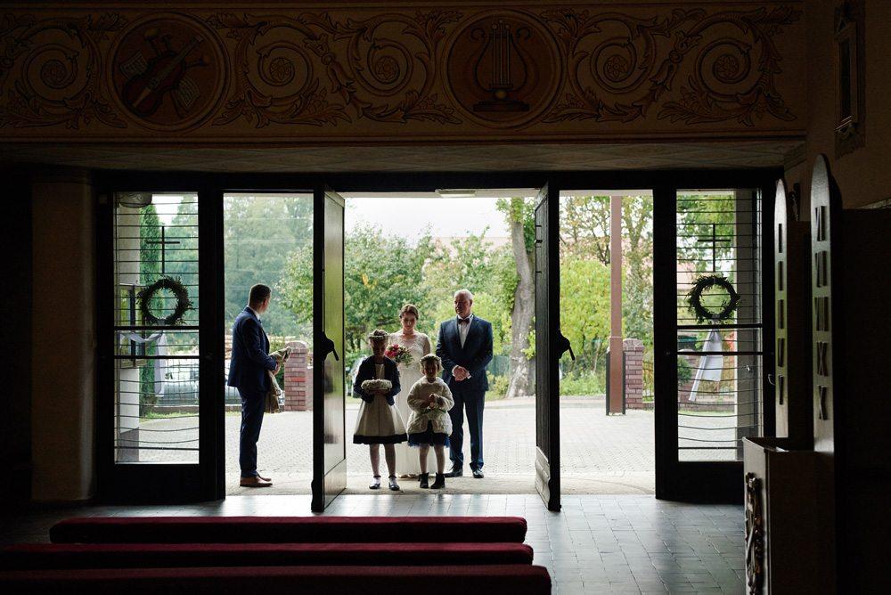 pani młoda czeka z ojcem w wejściu przed nimi dwie dziewczynki w wiankach