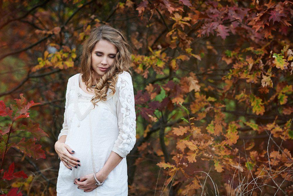 piękna sesja ciążowa jesienią - kobieta w bieli na tle jesiennych kolorów